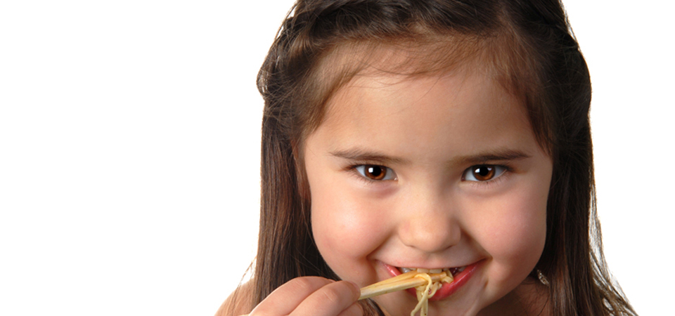 Little girl eating with chop-sticks
