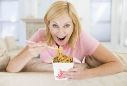 Smiling woman eating Chinese food with chop-sticks