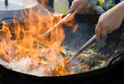 Cooking food in wok with flame fire
