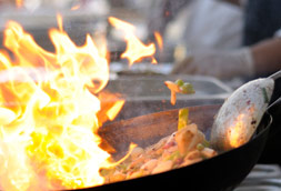 Cooking food in wok fire flame