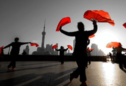 Shanghai China skyline with people dancing holding red cloth